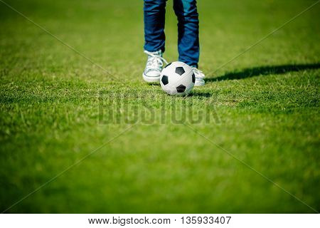 Boy playing football, teenager's legs with a ball on green grass field, soccer team player, training on the stadium, active lifestyle, sport background