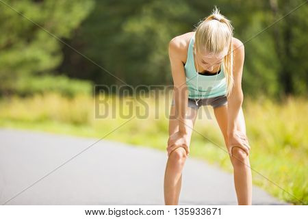 Young athletic woman runner rests after stamina training outdoor in the forest. Exhausted girl holding her hands on the knees.