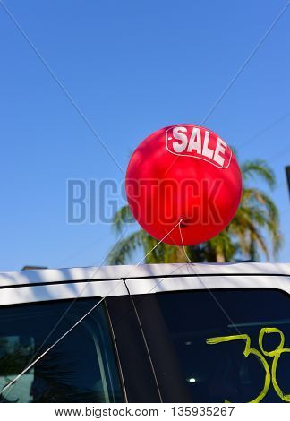 A used car lot uses colorful balloons to attract customers.