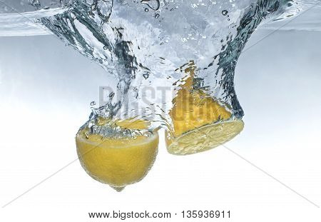Lemon fruits drop in water with splashes