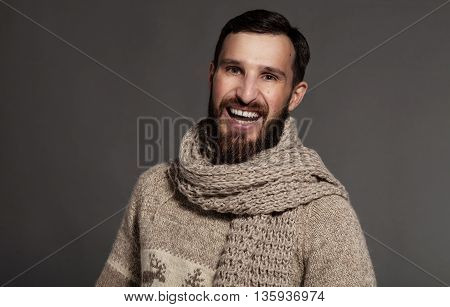 Smiling young bearded man on gray background