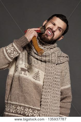 Making his beard perfect. Confident young bearded man shaving with ax and looking at camera while standing against grey background
