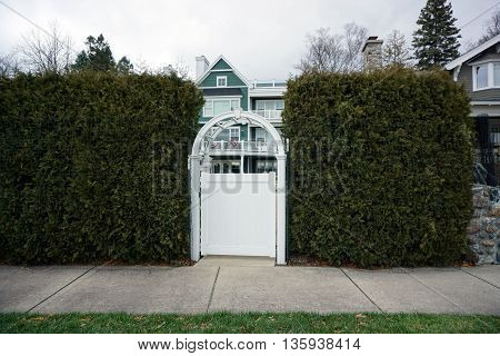 The gateway to a condominium building, with a tall arborvitae (Thuja occidentalis) hedge, near the Zorn Park Beach in Harbor Springs, Michigan.