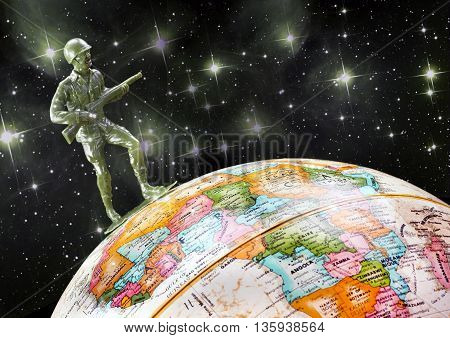 Green toy soldier on top of the world globe.