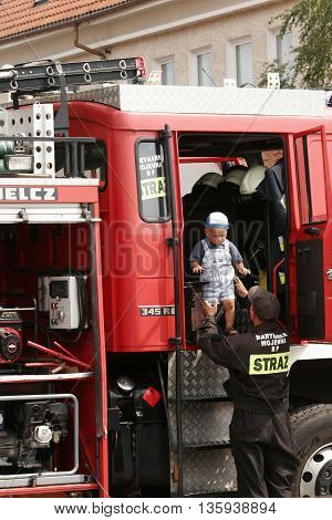 Jastarnia Poland August 15 2007: Festival City the presentation of firefighting equipment . Fireman helping the child to get out of the car combat