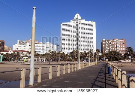 Empty Pier Leading Toward Residential And Comercial Buildings