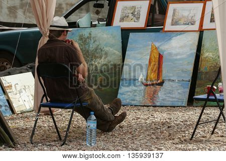 Jastarnia Poland August 15 2007: street vendor admires the painting exhibited at the outdoor exhibition