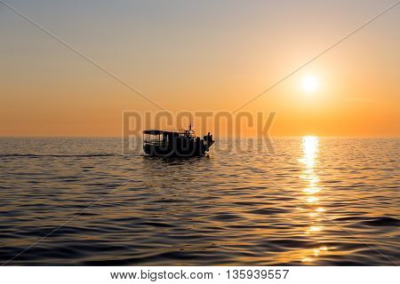 Ferry boat silhouette with people passengers at sunset sun in mediterranean sea