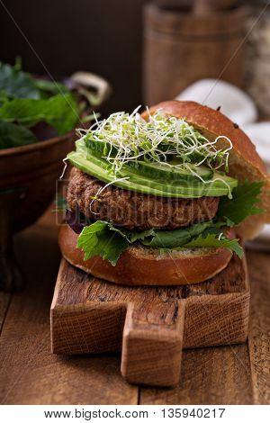 Grilled vegan bean burger with avocado, salad and cucumber
