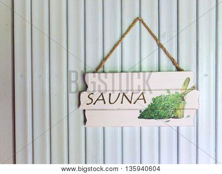 A wooden sauna sign on a wood panel door.