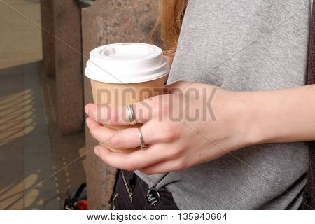Takeaway coffee cup in young woman hand instagram effect closeup shot.