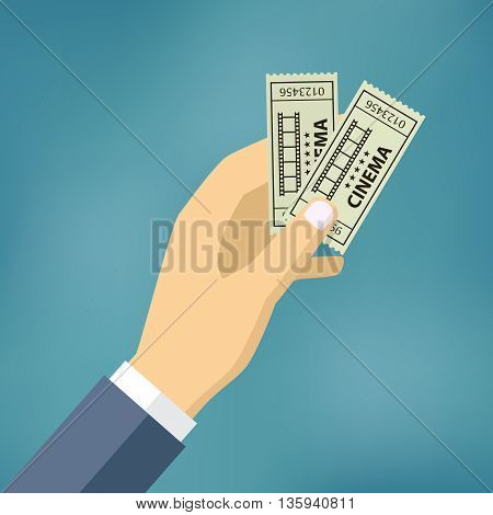 Hand holding or showing two cinema tickets.
