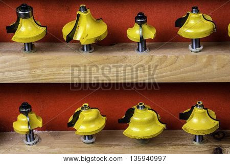 wooden shelf of assorted yellow metal router bits on red background