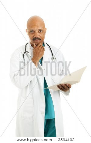 Serious african-american doctor considers treatment options while reviewing a patient's medical chart.  Isolated on white.