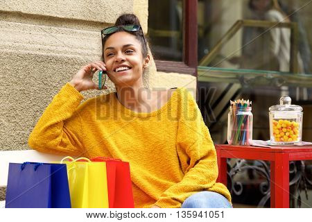 Female Shopper Sitting Outdoors And Using Mobile Phone