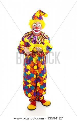 Full body isolated view of a birthday clown holding a balloon animal.
