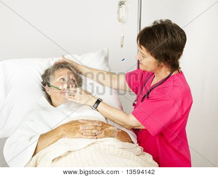 Hospital nurse helps a senior woman breath through an oxygen mask.