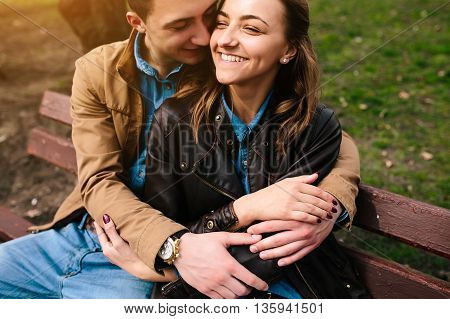 beautiful young couple relaxing on a bench in the park