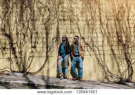 handsome guy and pretty girl posing on a background of a wall overgrown