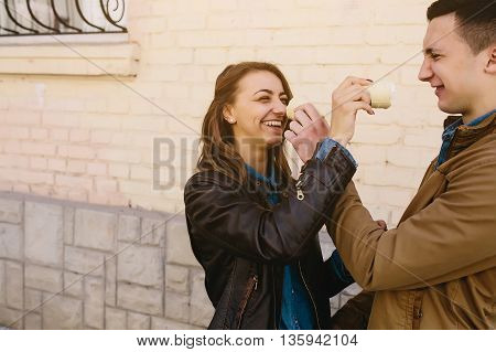 handsome guy and beautiful girl playing with ice cream on background wall