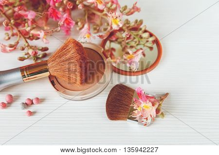 The Pink  Branches of Chestnut Tree,Bronze Powder with Mirrow and Make Up Brush are on White Table