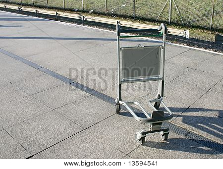 An abandoned trolley by the railway at an airport