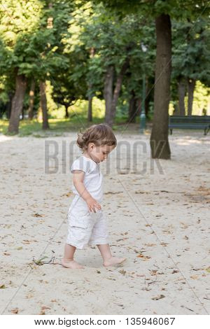 Little curly boy in T-shirt and shorts walking on the sand in the park looking at his feet