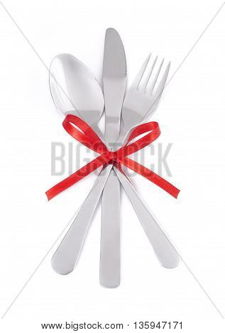 Crossed fork knife and spoon on white background with red ribbon.