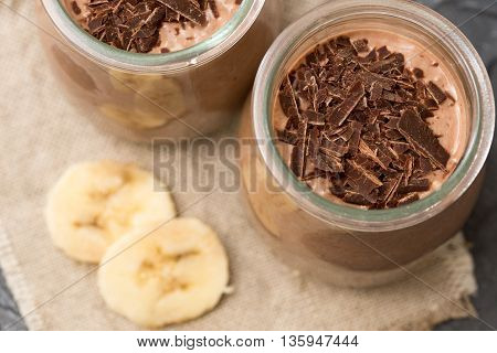Chocolate pudding with chia seed bananas and nuts in a glass jar.