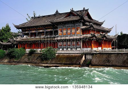 Dujiangyan China - October 9 2013: Historic tea house with orange lattice work windows and flying eave roofs sits beside the rushing waters of the Min River