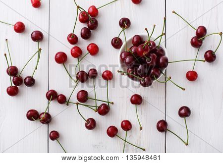 Sweet fresh cherries in a bowl and scattered on white rustic wood background. Fruits healthy food top view.