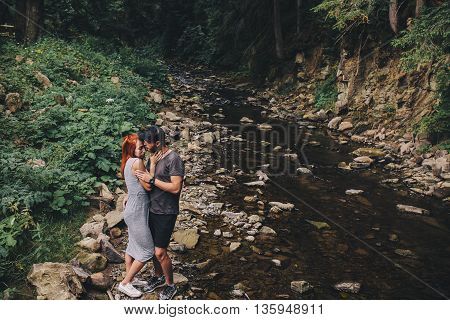 beautiful couple hugging each other near a mountain river