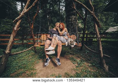 beautiful couple together with a dog resting on a swing
