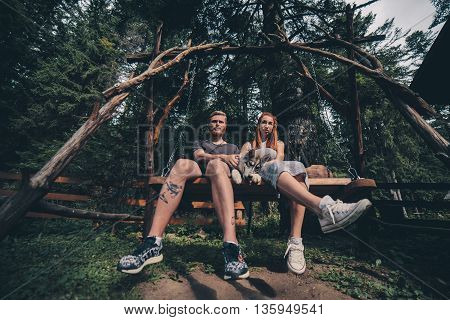 beautiful couple together with a dog resting on a swing. Picture taken from below