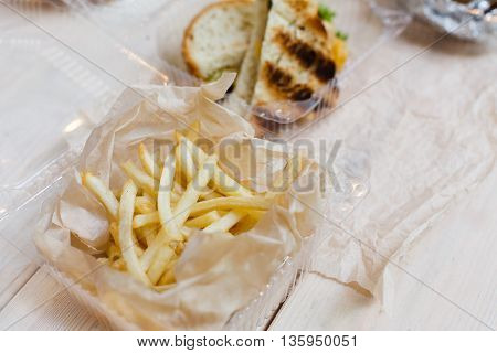French fries wrapped in paper. Portion in disposable plastic container at wooden table. Picnic food take away closeup