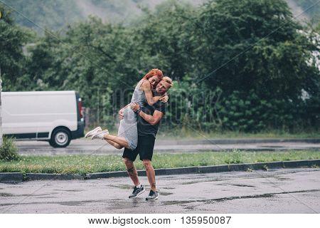 man throws up his girlfriend in the rain
