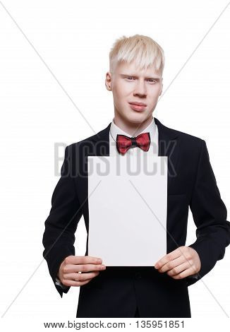Albino young man portrait holding empty paper sheet for copy space. Blond pale guy in suit with red bow tie isolated at white background. Stylish male person shows place for text