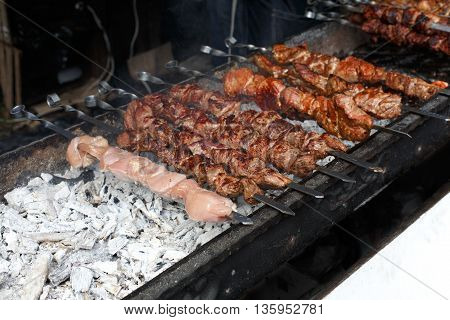 Raw kebab grilling on metal skewer. Raw meat roasting at barbecue. BBQ fresh beef and chicken chop slices. Traditional eastern dish, shish kebab. Grill on charcoal and flame, picnic, street food