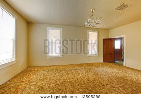 A Very Old Empty Living  Room With Yellow Walls