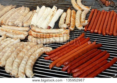 Sausage party. Barbecue large grill outdoors. Cookout bbq food. Big roasted pork bratwurst german sausages, white polish kielbasa. Meat grilled meal. Street food, fast food. Tasty snack, sausages.