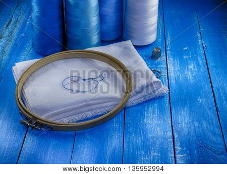 White fabric and thread in blue on vintage wooden table toning