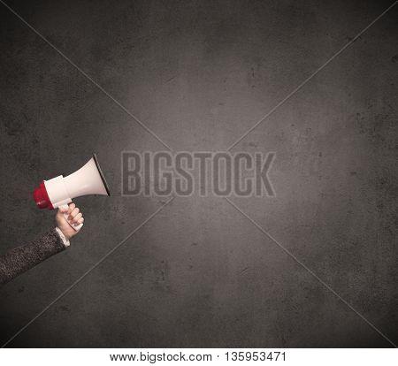 Caucasian arm holding megaphone with plain grunge background