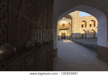 Wooden door and archway with the madarash building in the background.