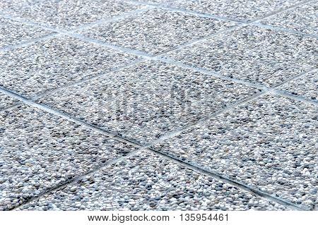 Detailed shot of pebbled tiles outdoors terrace flooring