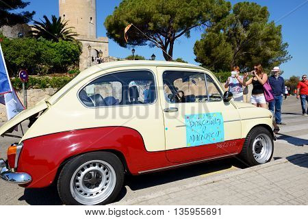 MALLORCA SPAIN - MAY 30: The SEAT 600 classic car parade and tourists on May 30 2015 in Mallorca Spain. Up to 60 mln tourists is expected to visit Spain in year 2015.