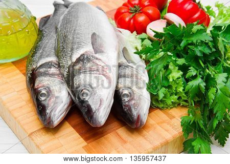 fresh see bass with some ingredients on wooden cutting board