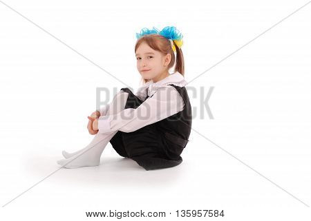 Girl in school uniform sitting and smiling isolated on white