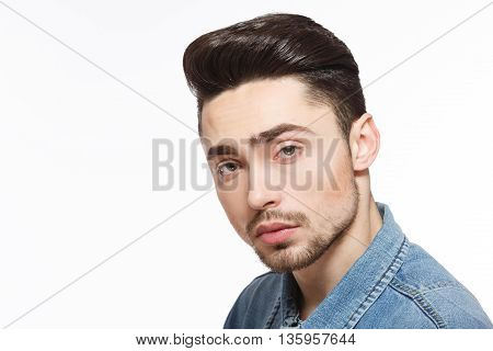Handsome model man posing over white background demonstrating his black hair forfashion magazine in studio. Modern hairstyle concept.