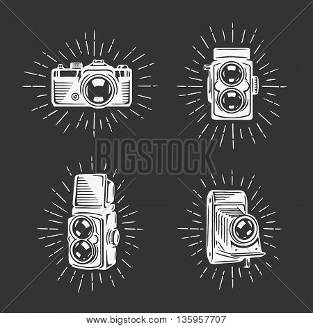 Retro photo cameras set. Design elements for photography related advertising, t-shirt prints, labels, badges, posters. Signs for photographer logo. Hand drawn vector vintage illustration.