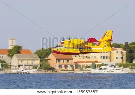 SIBENIK CROATIA August 6 2012 - Bombardier 415 Superscooper (Canadair cl-415) scooping water in tight channel near Sibenik